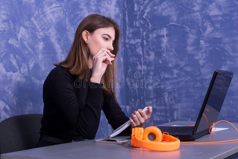 Donna di affari che lavora ad un computer portatile e che scrive in un taccuino, lavoro distante fotografia stock libera da diritti