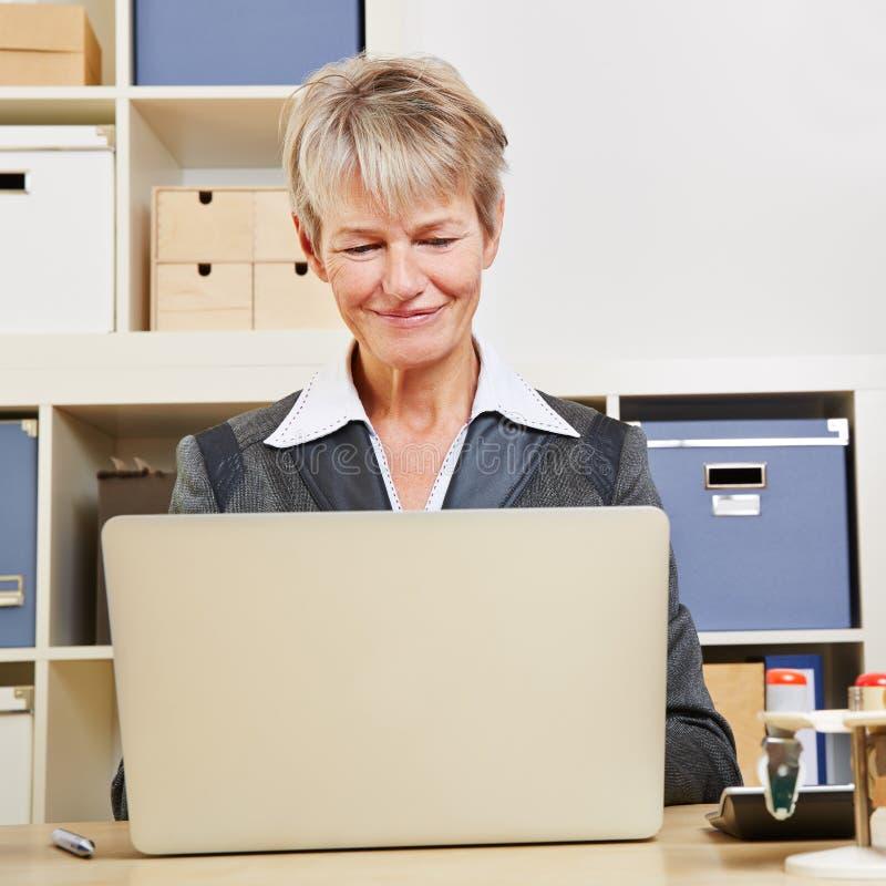 Donna di affari che lavora al computer portatile immagini stock