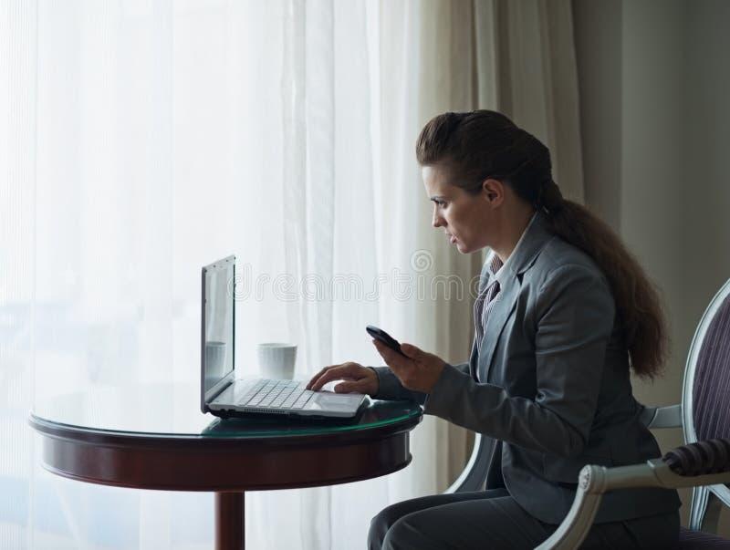 Donna di affari che lavora al computer portatile nella camera di albergo immagine stock