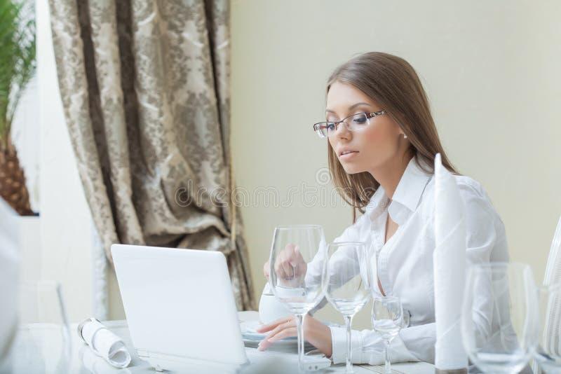 Donna di affari che lavora al PC in ristorante fotografia stock libera da diritti