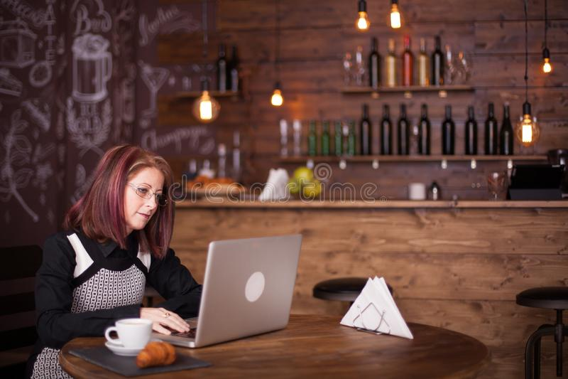 Donna di affari che lavora al suo computer portatile in una caffetteria accogliente fotografie stock libere da diritti