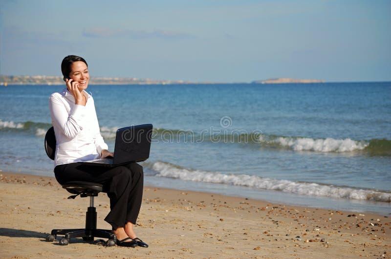 Donna di affari che lavora alla spiaggia immagini stock libere da diritti