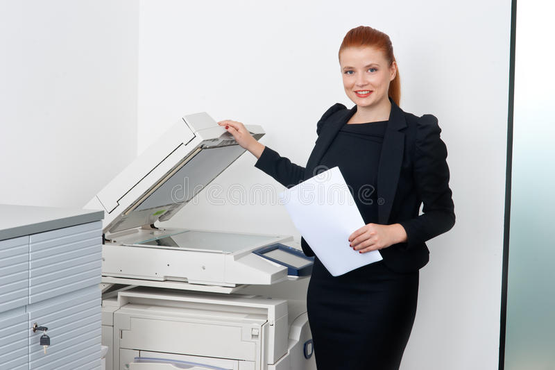 Donna di affari che lavora alla stampante di ufficio fotografie stock
