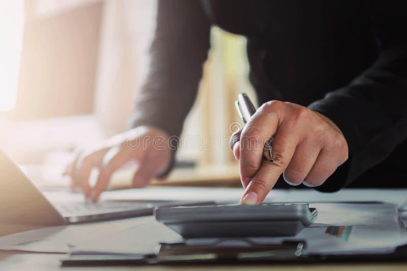 donna di affari che lavora allo scrittorio facendo uso del computer portatile per i dati del controllo di finanza fotografie stock libere da diritti