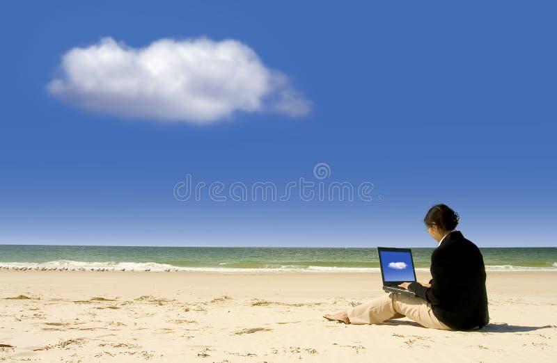 Donna di affari che lavora con il computer portatile alla spiaggia fotografie stock