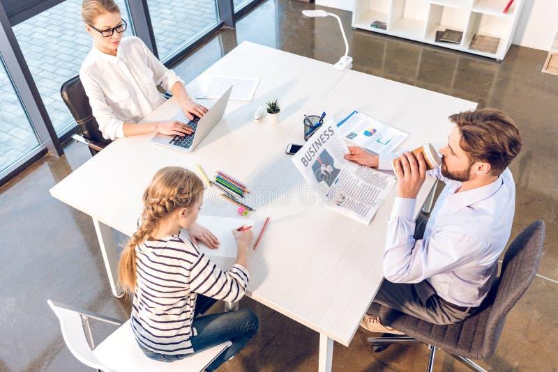 Donna di affari che lavora con il computer portatile, il giornale della lettura dell'uomo d'affari e avvicinarsi della figlia immagini stock libere da diritti