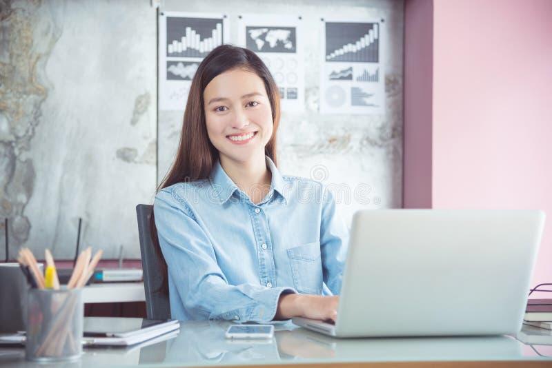 Donna di affari che lavora con il computer portatile in ufficio immagini stock libere da diritti