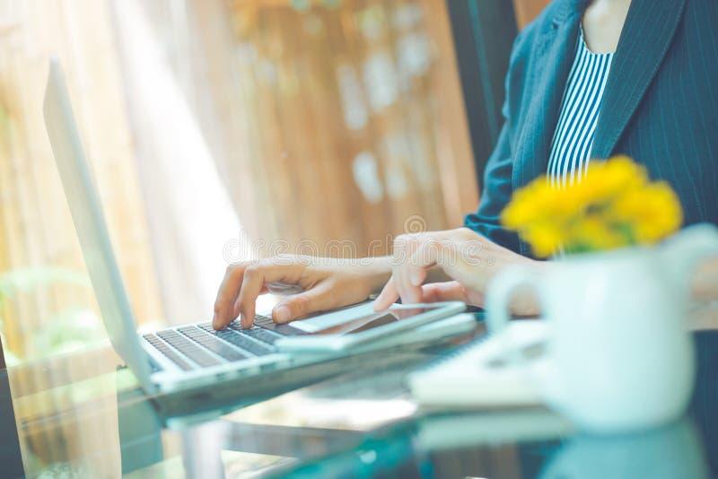 Donna di affari che lavora con il computer portatile in ufficio immagine stock