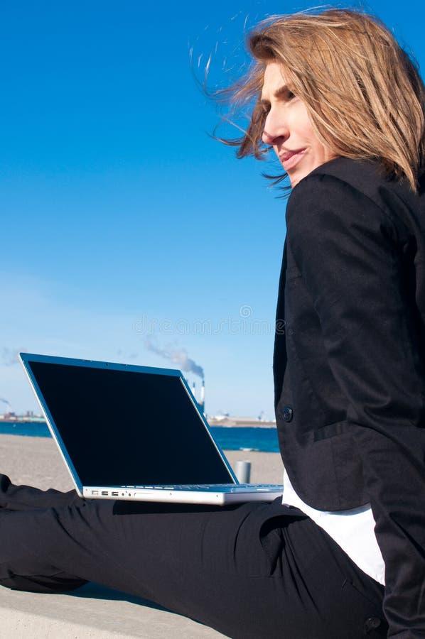 Donna di affari che lavora con il computer portatile, verticale fotografie stock