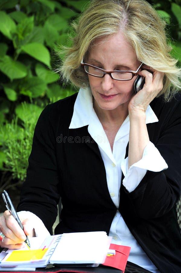 Donna di affari che lavora fuori fotografia stock
