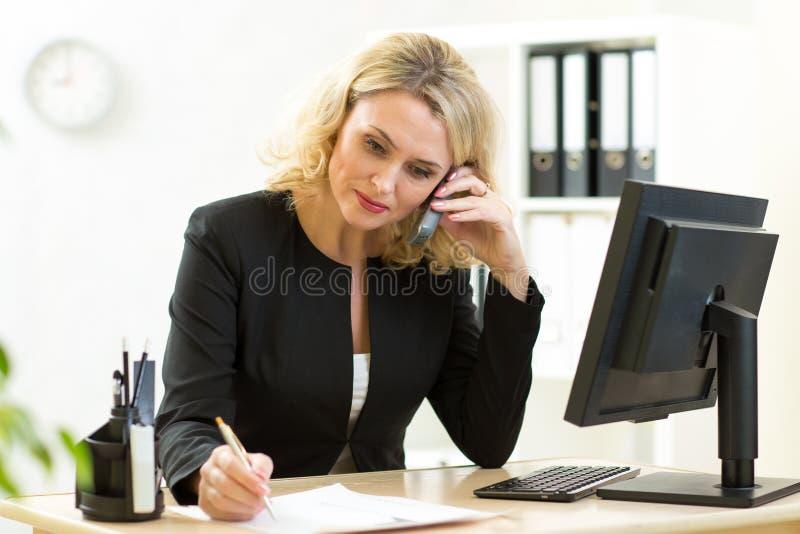 Donna di affari che lavora nell'ufficio Conversazione degli impiegati fotografie stock