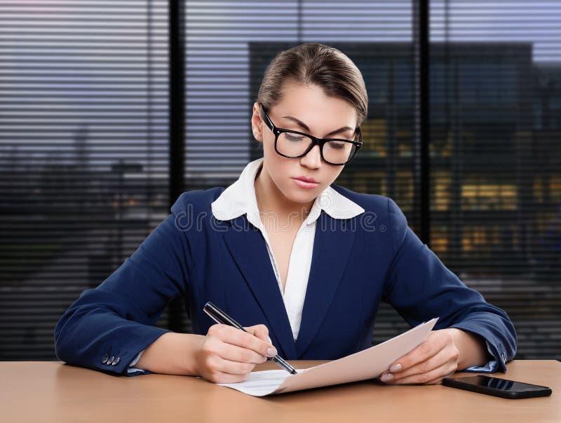 Donna di affari che lavora nell'ufficio, scrivente fotografia stock libera da diritti