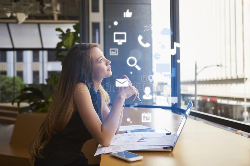 Donna di affari che lavora in un ufficio che esamina le icone di app fotografia stock libera da diritti