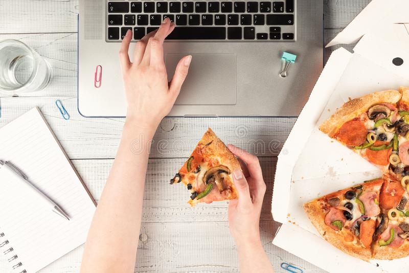 Donna di affari che lavora una scrivania con un computer portatile e che ha un pranzo fotografie stock