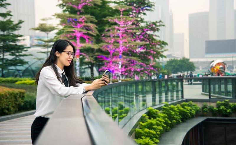 Donna di affari che manda un sms nell'ambiente moderno immagine stock