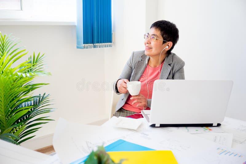 Donna di affari che mangia caffè fotografia stock libera da diritti