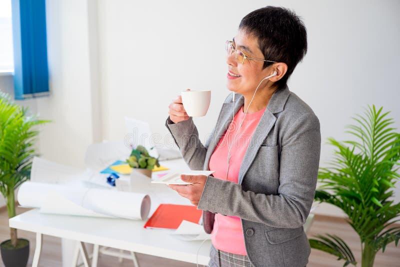 Donna di affari che mangia caffè immagini stock libere da diritti