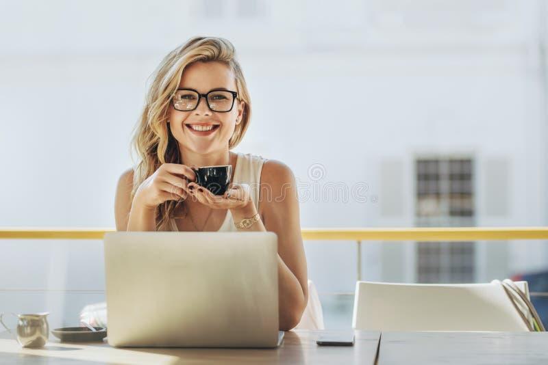 Donna di affari che mangia caffè a coffeeshop immagine stock libera da diritti