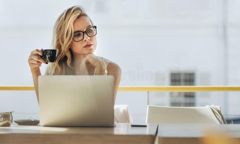 Donna di affari che mangia caffè e che pensa al caffè fotografie stock libere da diritti
