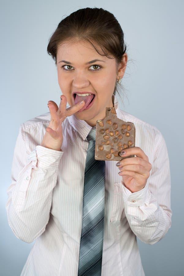 Donna di affari che mangia cioccolato fotografie stock