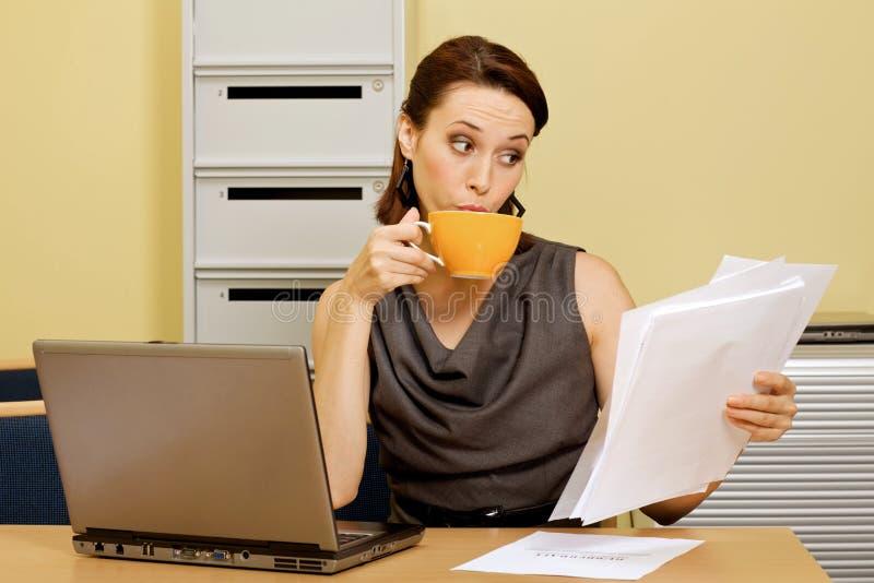 Donna di affari che mangia tè mentre esaminando i documenti in ufficio fotografia stock