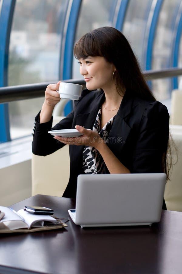 Donna di affari che mangia una tazza di tè immagine stock libera da diritti