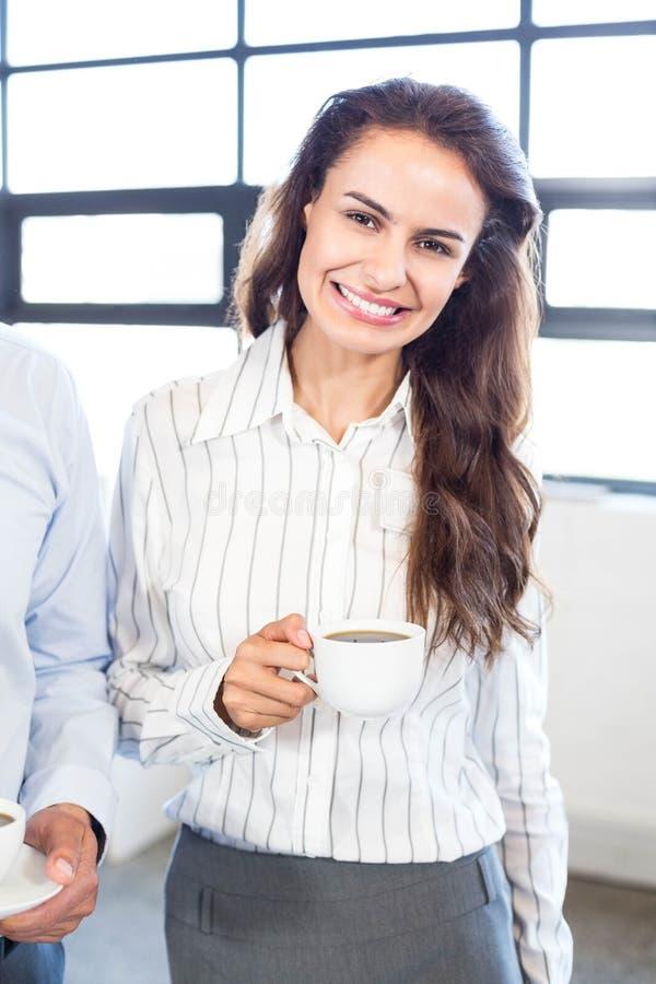 Donna di affari che mangia una tazza di tè fotografia stock libera da diritti