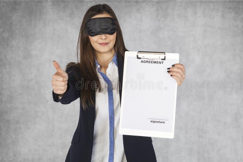 Donna di affari che mostra i pollici giù, bendato gli occhi fotografie stock