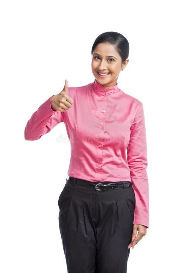 Donna di affari che mostra il segno del pollice fotografia stock