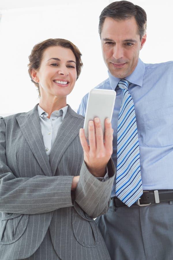 Donna di affari che mostra qualcosa al suo collega sul suo smartphone immagini stock