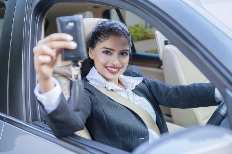 Donna di affari che mostra un'automobile per digitare l'automobile immagini stock