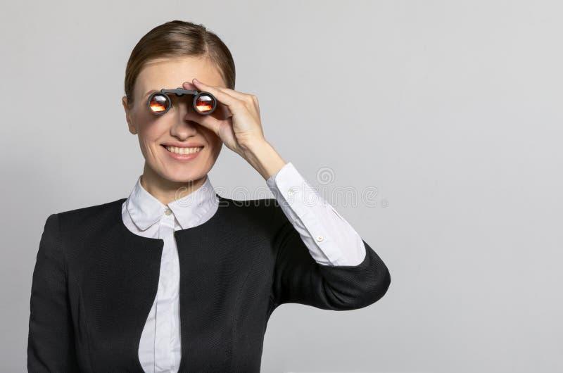 Donna di affari che osserva tramite il binocolo immagine stock