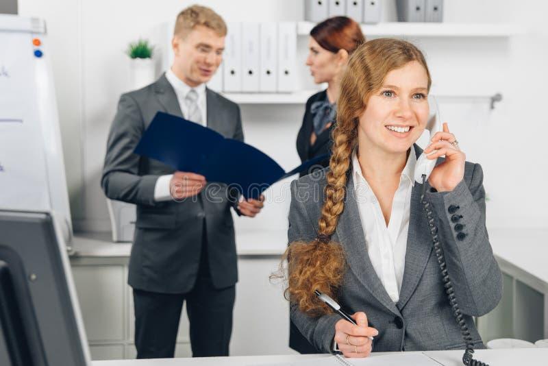 Donna di affari che parla al telefono in ufficio fotografia stock