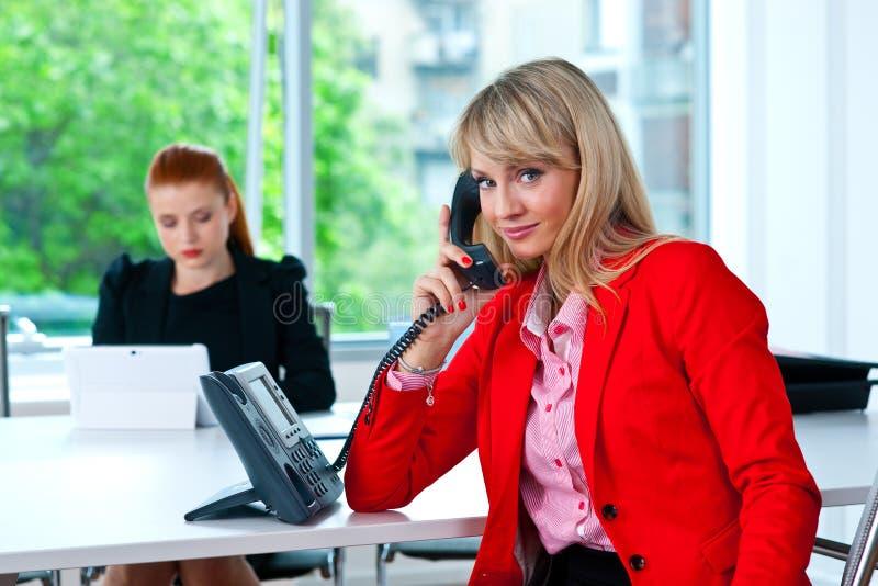 Donna di affari che parla con telefono con il collega nel fondo fotografia stock