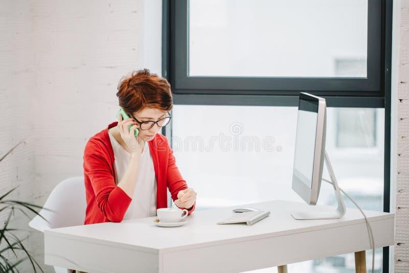 Donna di affari che parla sullo Smart Phone all'ufficio fotografie stock libere da diritti