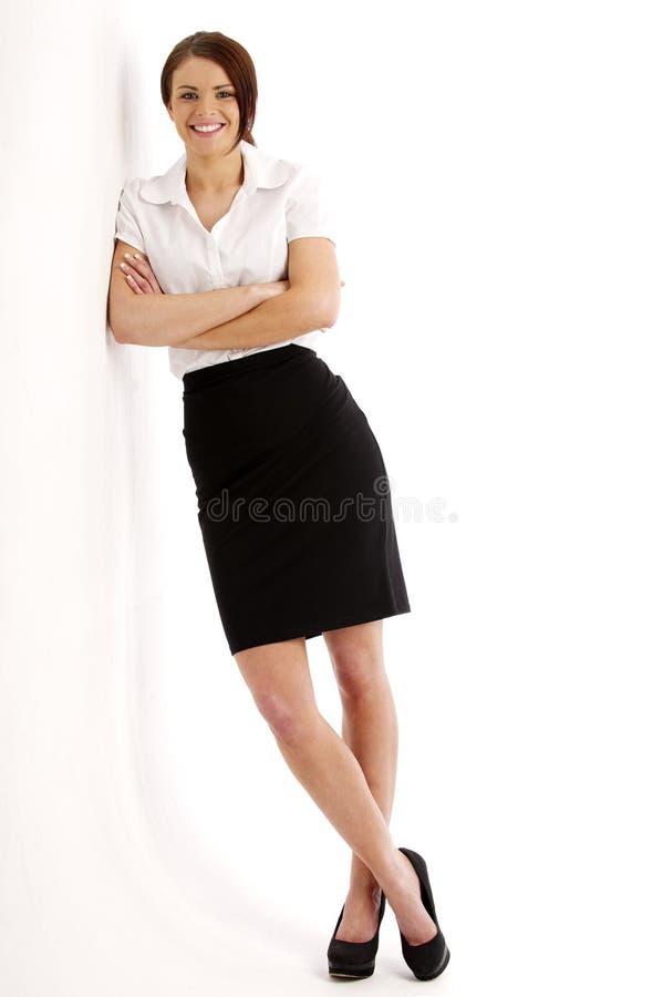 Donna di affari che pende contro una parete fotografia stock