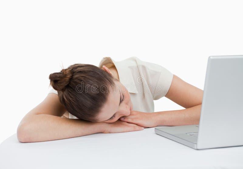Donna di affari che pende sul suo scrittorio con un computer portatile fotografie stock