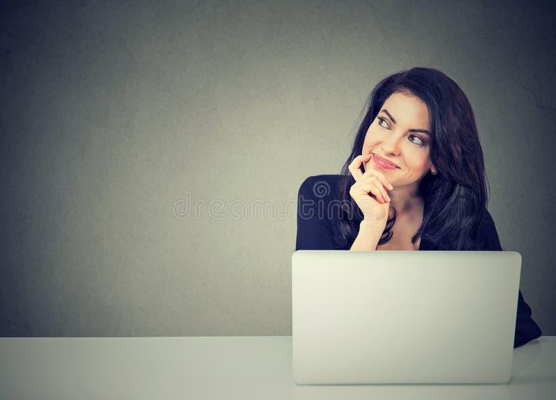 Donna di affari che pensa fantasticando seduta allo scrittorio con il computer portatile fotografie stock