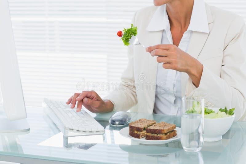Donna di affari che per mezzo del computer mentre mangiando insalata allo scrittorio fotografia stock