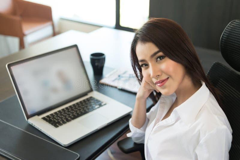 Donna di affari che per mezzo del computer portatile all'ufficio fotografie stock