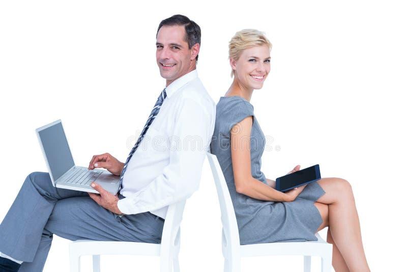 Donna di affari che per mezzo del computer portatile e della compressa immagini stock