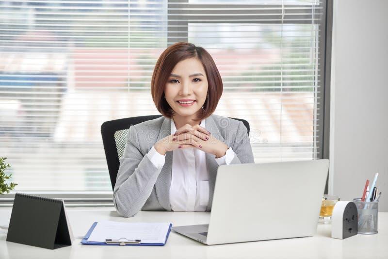 Donna di affari che per mezzo del suo computer portatile all'ufficio Gente di affari immagine stock