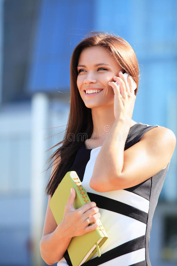 Donna di affari che per mezzo del telefono cellulare fotografia stock