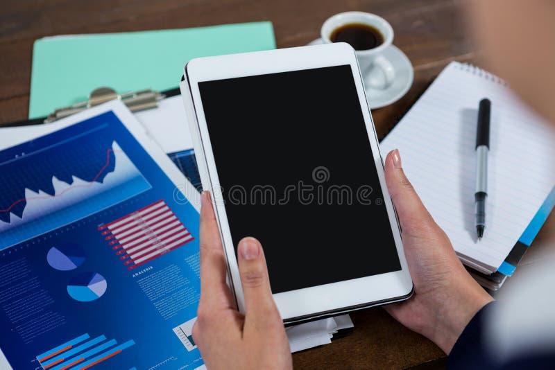 Donna di affari che per mezzo della compressa digitale con il grafico del grafico sulla tavola immagini stock