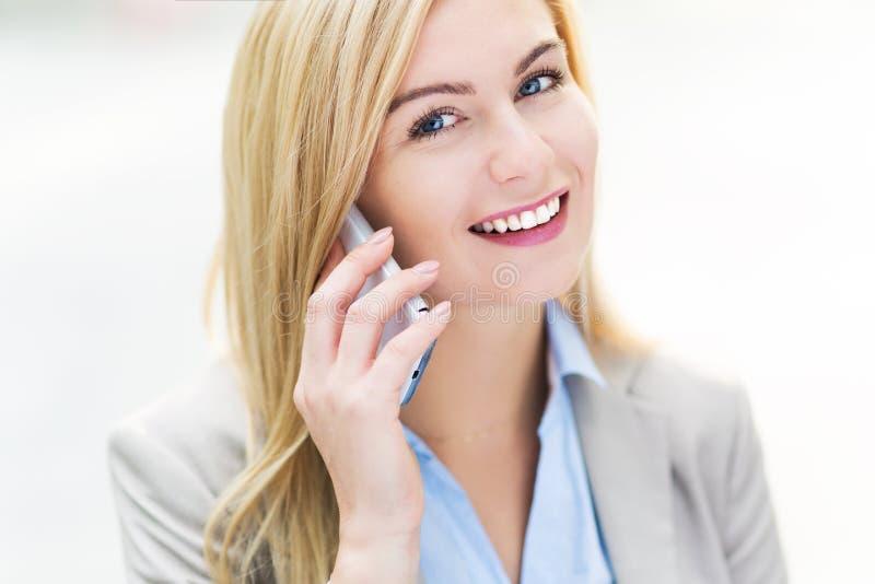 Donna di affari che per mezzo di un telefono mobile fotografie stock libere da diritti