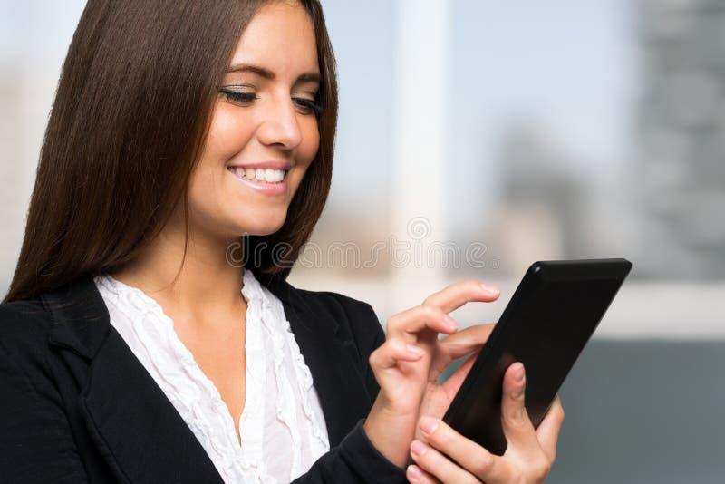 Donna di affari che per mezzo di una compressa digitale immagini stock libere da diritti