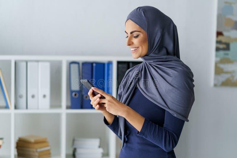 Donna di affari che per mezzo di un telefono fotografia stock