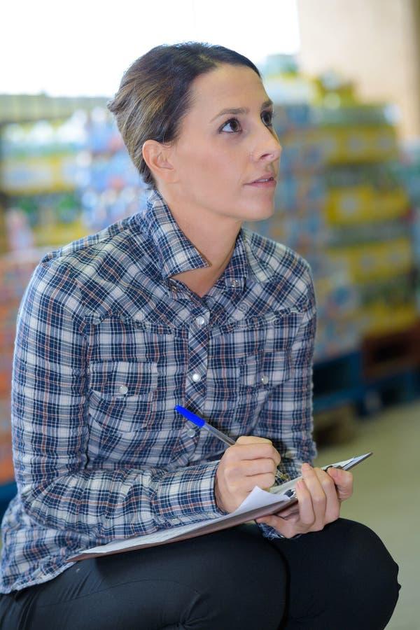 Donna di affari che posa con la lavagna per appunti in magazzino immagine stock