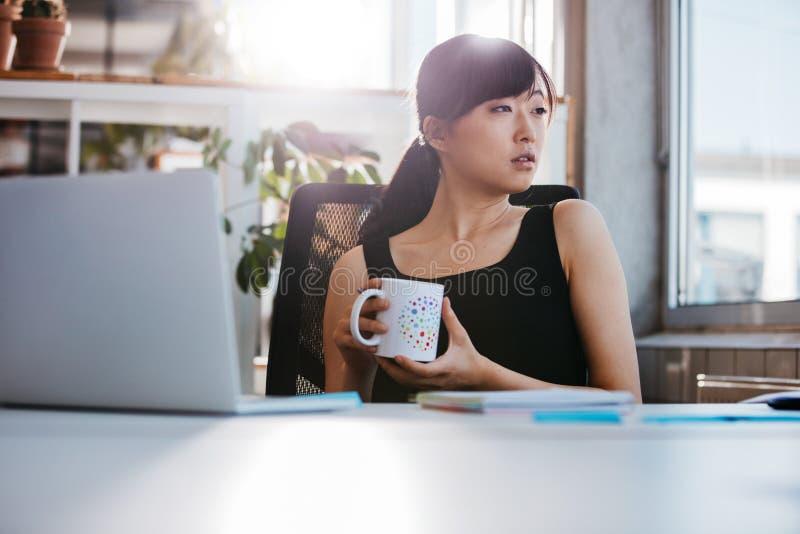 Donna di affari che prende pausa caffè in ufficio immagine stock