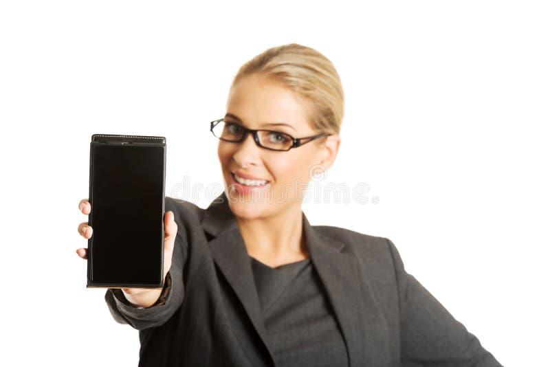 Donna di affari che presenta telefono cellulare immagine stock libera da diritti